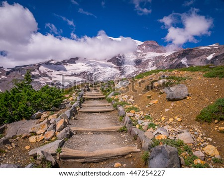 Rocky slopes in the mountains. Amazing view at the peaks which rose against the cloud sky. Path on the tops of mountains. Mount Rainier National Park,  Skyline trail - stock photo