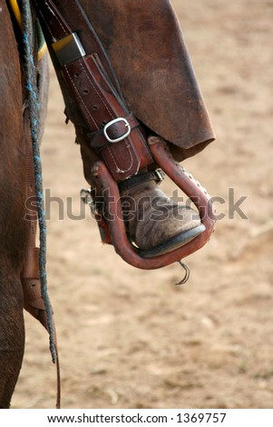 rodeo riders boot and leathers in stirrup - stock photo