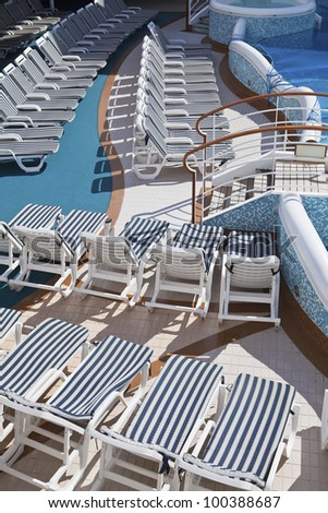 Roes of striped deck chairs by the pool on sundeck of the cruise ship on sunny day - stock photo