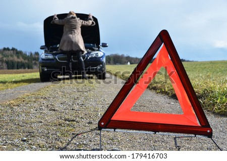roken car, girl and warning triangle  - stock photo
