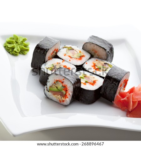 Roll made of Fresh Salmon, Smoked Eel, Avocado, Tobiko and Cucumber inside. Nori outside - stock photo