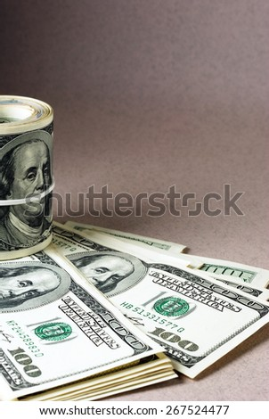 Roll of hundred-dollar bills bounded by rubber band. Vintage dollar background - stock photo