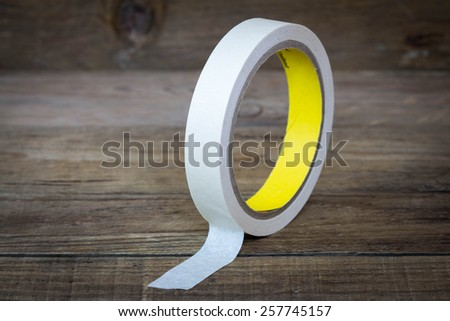roll of masking tape on wood. - stock photo