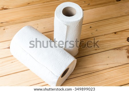 Roll of paper towel on wooden background - stock photo