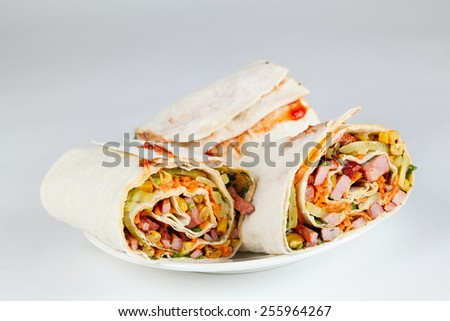Roll of roast meat with corn and vegetables in a pita. - stock photo