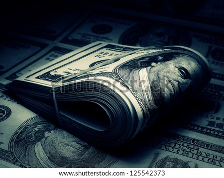 Roll of US dollars in dark style. Blue tone. - stock photo