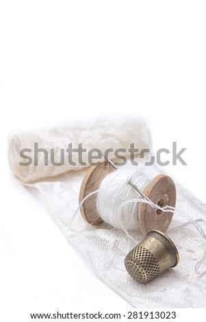 roll of white lace, a wooden spool of white cotton thread for sewing with needle and a metal thimble on white background - stock photo