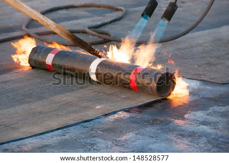 Roll roofing Installation with propane blowtorch during construction works - stock photo