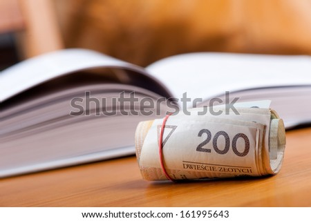 Rolled bunch of money two hundred polish zloty banknotes and open book blurred behind, object on table in horizontal orientation, nobody. - stock photo