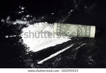 rolled dollar with cocaine heap on black table  - stock photo