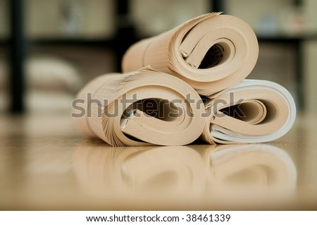 Rolled education book on the wood table - stock photo