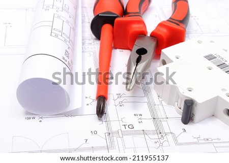 Rolled electrical diagrams, electric fuse and work tools lying on construction drawing of house, drawings for the projects engineer jobs - stock photo