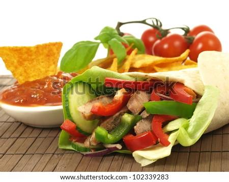 Rolled fajita with salsa on wooden pad - stock photo