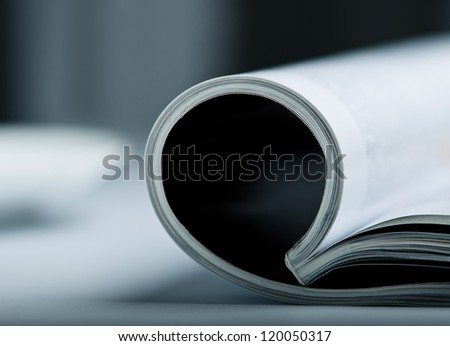 Rolled glossy magazine on a table with very shallow depth of field. - stock photo