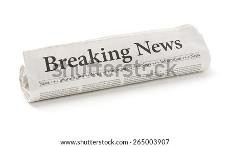 Rolled newspaper with the headline Breaking news - stock photo