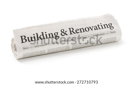 Rolled newspaper with the headline Building and Renovating - stock photo