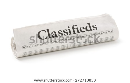 Rolled newspaper with the headline Classifieds - stock photo