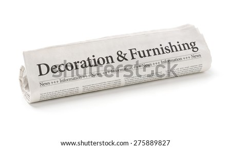 Rolled newspaper with the headline Decorating and Furnishing - stock photo