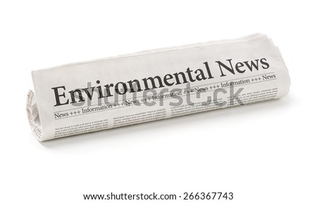 Rolled newspaper with the headline Environmental News - stock photo