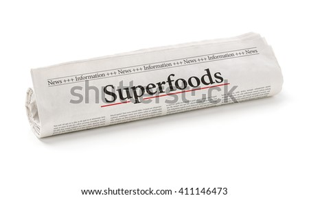 Rolled newspaper with the headline Superfoods - stock photo