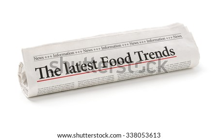 Rolled newspaper with the headline The latest Food Trends - stock photo