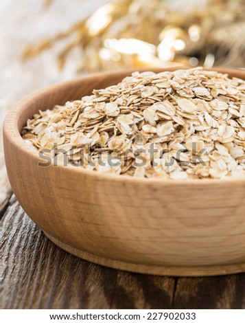 Rolled oat flakes in a wooden bowl and oat stalks - stock photo