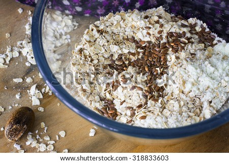 rolled oats and flax seeds in a glass bowl. selective focus - stock photo