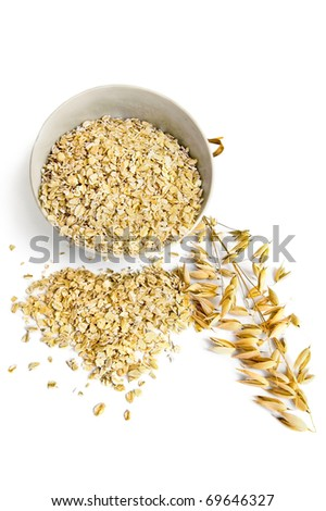 Rolled oats in a bowl on the table in the form of hearts, ripe stalks of oats isolated on a white background - stock photo