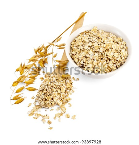 Rolled oats in a wooden spoon and a white porcelain bowl, oat stalks isolated on white background - stock photo