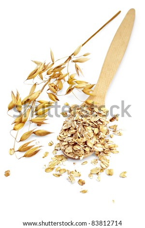 Rolled oats in a wooden spoon, stalks of oats is isolated on a white background - stock photo