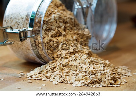 rolled porridge oats falling out of a glass jar - stock photo