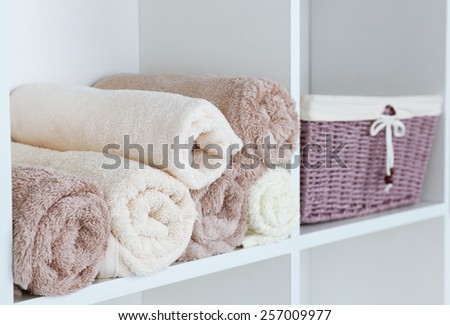 Rolled towels with wicker basket on shelf of rack background - stock photo