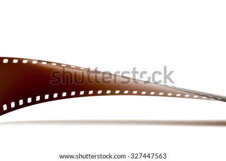 Rolled undeveloped film strip with shadow. - stock photo