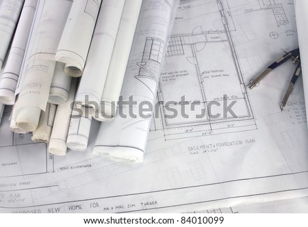 Rolled up Blueprints and Drawings with Compass - stock photo