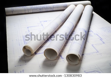 rolled up blueprints sitting on an unrolled blueprint - stock photo