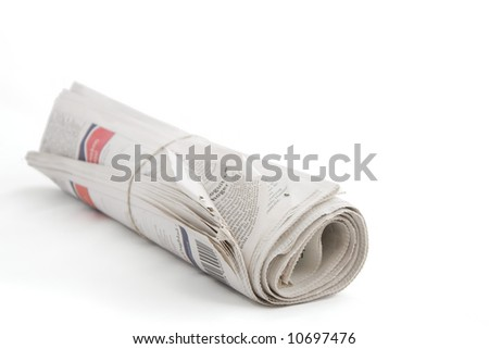 rolled up Dutch Newspaper with rubber band against plain background shot with very shallow depth of field    - stock photo