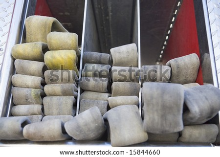 Rolled up fire hose in a fire engine - stock photo
