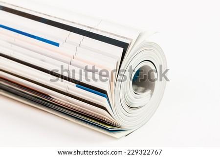 rolled up magazine - on white background - stock photo
