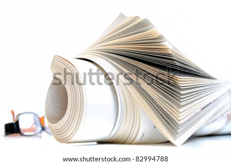 Rolled up magazine with white cover and glasses in background - stock photo