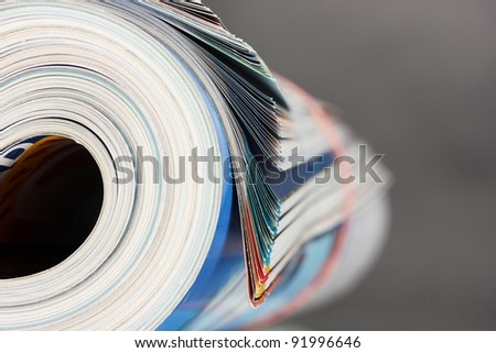 Rolled up magazines on gray background - stock photo