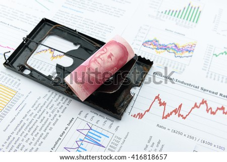 Rolled up scroll of CNY Chinese yuan 100 bill as a bait on a black rat trap. A symbol of using money / currency to lure someone to do illegal / dishonest / fraudulent things i.e. corruption, bribery - stock photo