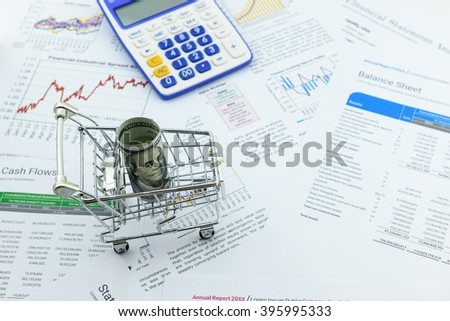 Rolled up scroll of US 100 dollar bill in a trolley on financial reports with a calculator. A concept of the significance of dollar currency which dominate every countries in the world. - stock photo