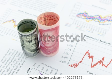 Rolled up scrolls of US dollar bill and Chinese Yuan with image / portrait of President Mao Zedong and Benjamin Franklin. Placing on financial reports with several charts i.e. colored linear graph. - stock photo