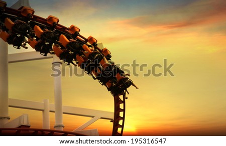 Roller Coaster loops in the sunset - stock photo