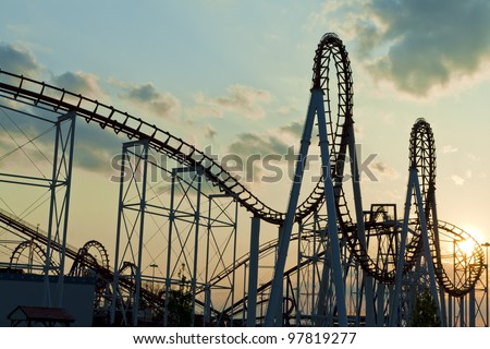 Roller Coaster loops in the sunset. - stock photo
