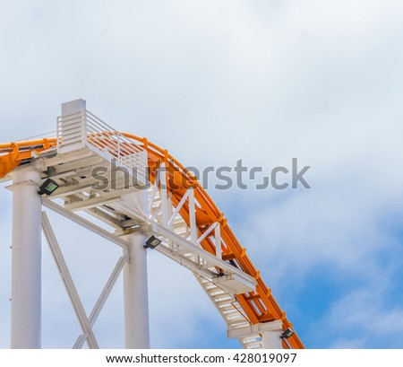 Roller coaster ride in a clear blue sky day - stock photo