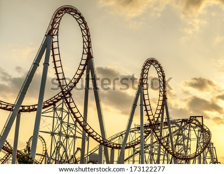 Roller Coaster's loops at sunset. - stock photo