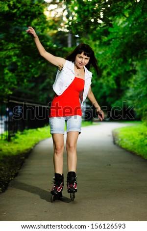 Roller skating girl in park rollerblading on inline skates - stock photo