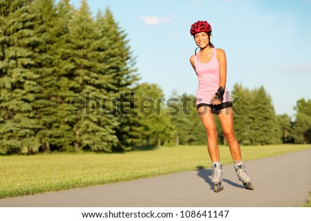 Roller skating girl in park rollerblading on inline skates. Mixed race Asian Chinese / Caucasian woman in outdoor activities. - stock photo