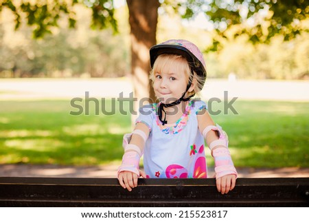 Roller skating happy little blond girl - stock photo